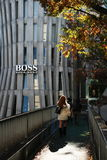 People cross footbridge in front of Hugo Boss, flagship store, Tokyo Stock Image