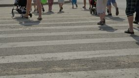 People cross the road on a pedestrian crossing. Close-up crosswalk stock footage