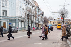 People cross the road at pedestrian crossing. Stock Image