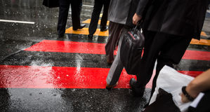 People cross street at rainy day Stock Images