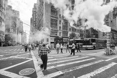 People cross the West 57th Street passing a vaporous steam pipe. New York, USA - May 26, 2017: People cross the West 57th Street passing a vaporous steam pipe Royalty Free Stock Photography