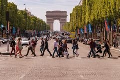 People crossing Avenue des Champs-Elysees in Paris. Paris, France - 23 June 2018: A crowd of people crossing Avenue des Champs-Elysees with Arc de Triomphe in royalty free stock photo
