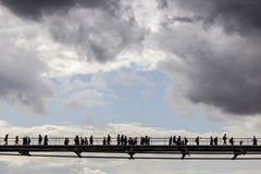 People crossing a bridge, over the Thames river Stock Image