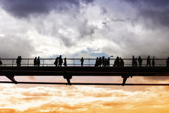 People crossing a bridge, over the Thames river Stock Images