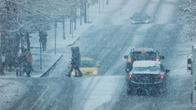 People Crossing Busy Road In Snowstorm stock footage