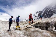 People Crossing Glacier Crevasse on Wood Shaky Footbridge Royalty Free Stock Photo