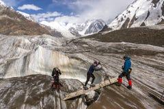 People Crossing Glacier Crevasse on Wood Shaky Footbridge Stock Photography