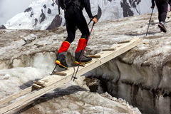People Crossing Glacier Crevasse on Wood Shaky Footbridge Stock Photos