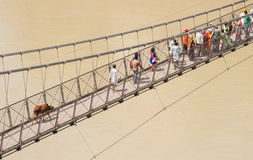 People crossing Laxman Jhula suspension bridge on river Ganga, R Stock Image