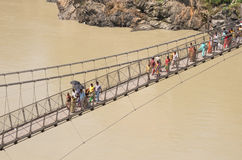 People crossing Laxman Jhula suspension bridge on river Ganga, R Royalty Free Stock Photos