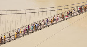 People crossing Laxman Jhula suspension bridge on river Ganga, R Stock Photo