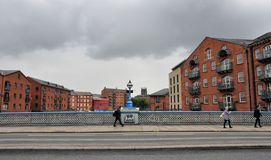 People crossing Leeds bridge with residential building on either side of the river aire. Leeds, England - November 23 2017: People crossing Leeds bridge with Stock Image