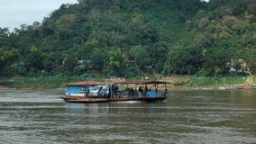 People crossing Mekong river by ferry. LUANG PRABANG - DECEMBER 22, 2016: People crossing Mekong river by ferry on december 22, 2016 in Luang Prabang, Laos. Full stock footage