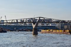 People Crossing the Millenium Bridge over the Thames stock photography