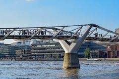 People Crossing the Millenium Bridge over the Thames stock photos
