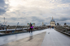 People crossing the Millennium Bridge on a Cloudy Day Royalty Free Stock Photos
