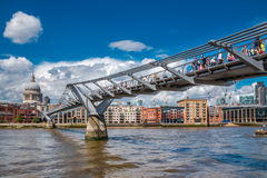 People crossing Millennium Bridge on a sunny day. People walking on Millennium Bridge in London with St. Paul's Cathedral in the background Royalty Free Stock Image