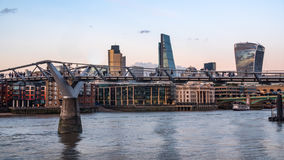 People crossing the Millennium bridge at sunset with the skyline of the City of London. In the background Stock Photography