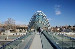 People crossing modern futuristic Bridge of Peace over Mtkvari River,Tbilisi, Georgia Stock Photo