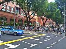 People crossing Orchard Road, Singapore. Crowd of people crossing Orchard Road at a traffic junction in Singapore Stock Images
