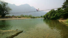 People crossing river on bamboo suspension bridge, vang vieng, laos stock video