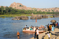 People crossing the river by boat at Hampi on India Stock Photo