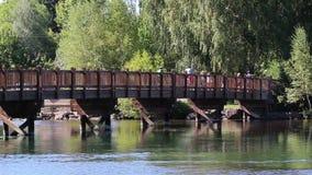 People Crossing River Bridge On Summer Day stock video