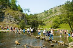 People crossing river Dove. Scenic view of people crossing river Dove with stepping stones, Dovedale Valley, Peak District, England Stock Photo
