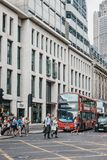 People crossing the road on a pedestrian crossing in front of red bus in City of London, UK. stock images