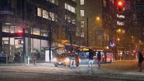 People Crossing Road In Snowstorm Downtown. Cars stop and people walk across road in the city on snowy night stock footage