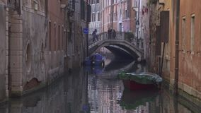 Small bridge at a canal in Venice with historic buildings stock video footage