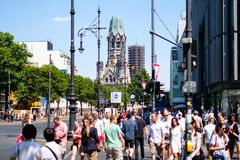 People crossing street at Berlin`s most famous shopping avenue,. Berlin, Germany - june 09, 2018: People crossing street at Berlin`s most famous shopping avenue Royalty Free Stock Images