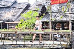 People crossing on wooden bridge in pattaya floating market stock photos