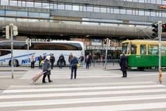 People at a crosswalk. Helsinki, Finland - October 13, 2016: People at a crosswalk in front City Central mall and tram stop in Helsinki, Finland Stock Photo