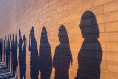 Free People Crowd Shadows Lined Up Against A Red Brick Wall. They Are In A Queue For Changes In Life. Social Distance, Covid Royalty Free Stock Photo - 182518075