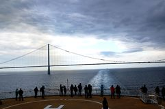 People on cruise ship looking at a bridge in the middel of the Ocean. The name of the bridge is `Øresund broen` Oresund bridge` and is Royalty Free Stock Photography