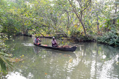 People cruising on a canoe a river of the backwaters. Kollam, India - 19 January 2015: People cruising on a canoe a river of the backwaters at Kollam on India Stock Photo