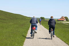 People cycling along the Dutch seawall of North Sea Royalty Free Stock Photography