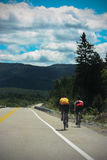 People cycling on a endless road. 2 people cycling on a endless road in the mountains Royalty Free Stock Images