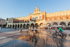 People cycling on the main market square of Cracow, Poland Stock Photography