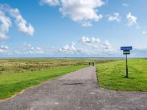 Free People Cycling On Bicycle Path Between Dike And Salt Marshes On Frisian Island Schiermonnikoog, Netherlands Royalty Free Stock Image - 164440416