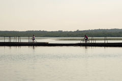 People cycling in the pier. Lake view Royalty Free Stock Image