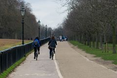 People cycling and walking in a tree lined street in Hyde Park London, late winter season. People cycling and walking in a tree lined street in Hyde Park London Royalty Free Stock Image
