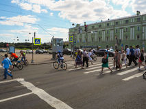 People and cyclists crossing the street. Urban everyday life in St. Petersburg. The Kutuzov Embankment. Russia. Summer 2017 Royalty Free Stock Image