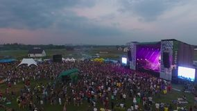 People dance at a music rock festival. Aerial view. Main stage.