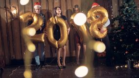 People dance near a Christmas tree with 2018 number shaped balloons. Men and women dance hugging huge balloons in shape of 2018 year number stock footage