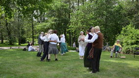 People dance in pairs and accordionist in park folk event stock footage