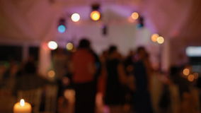 People dance on the party. Party out of focus, Candle on the first plan