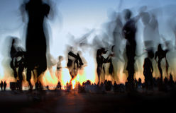 People dancing on the beach. Against the setting sun Royalty Free Stock Photo
