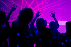 People dancing in club with laser. Silhouettes of dancing people having a celebration in a disco club, the light show is sending laser beams through the backlit Stock Photo